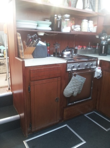 If you notice above the stove was a shelf that was closed in on one end. There used to be an exhaust fan but it quit so my brother took it out. I fixed the hole on the outside of the boat and then removed the closed in part and made it one big long shelf. It was no easy task and took me the better part of a day. But it gave so much more storage room and looks better i think. Plus the wood looks so much better too, don't you think?